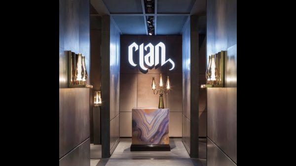 Fotografia dell'ingresso dello showroom di Clan Milano con lampade a candelabro color oro e logo del brand