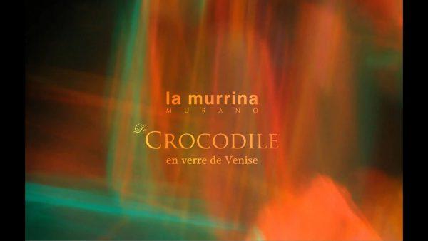 Frame di video teaser con sfondo di luci verdi e arancioni e logo de La Murrina Murano con titolo dello'opera Le Crocodile en verre de Venise
