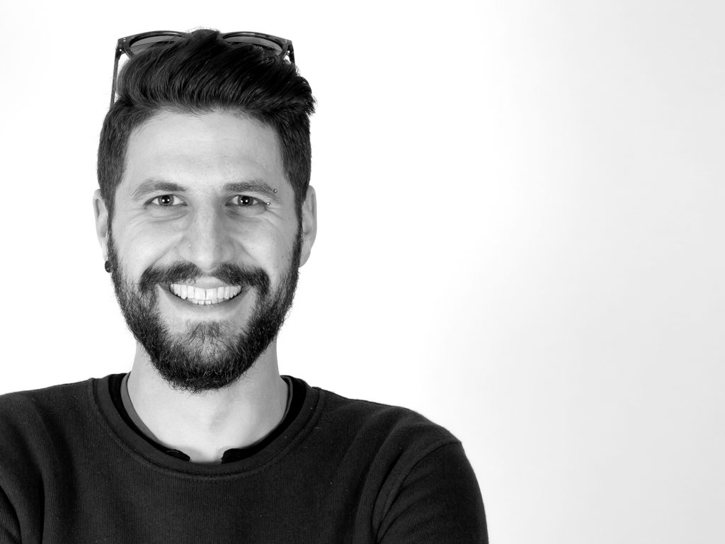 Fotografia in bianco e nero che ritrae il videomaker Antonio Sinfù mentre sorride