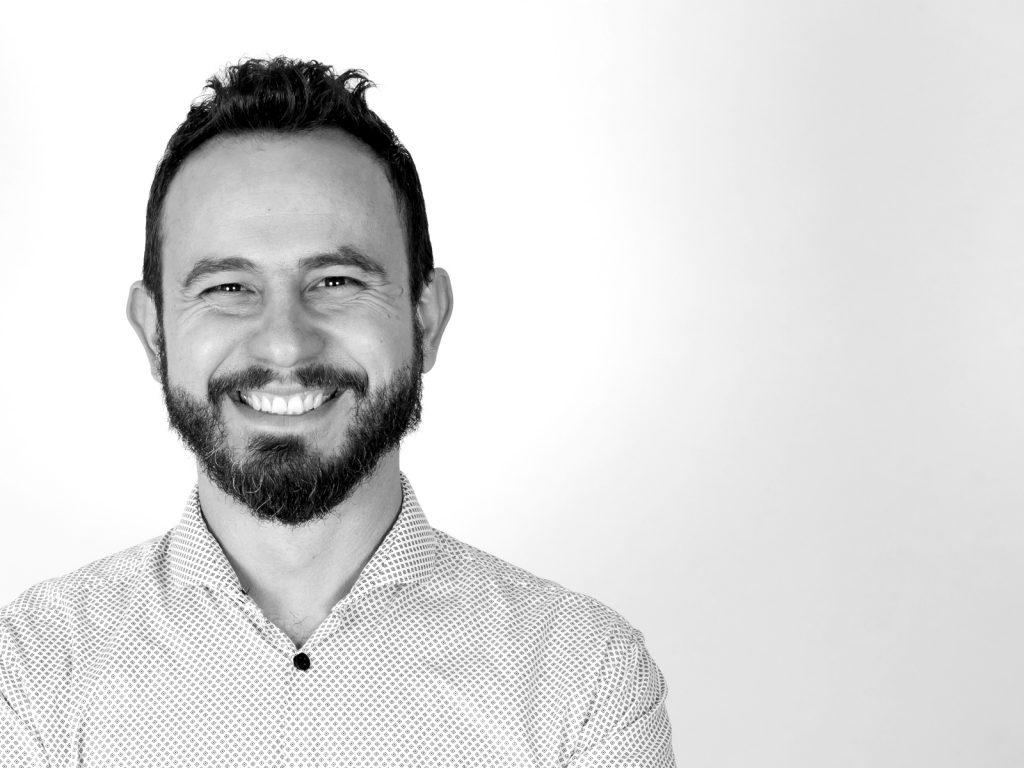 Fotografia in bianco e nero che ritrae il videomaker Diego Alberghini mentre sorride