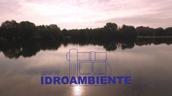 Fotografia di lago artificiale sull'acqua con alberi sulla riva, cielo nuvoloso e logo di idroambiente.it