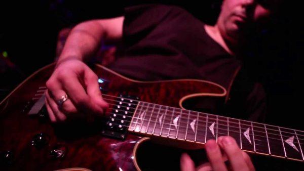 Fotografia di una chitarra e delle mani del chitarrista che la sta suonando durante un concerto live