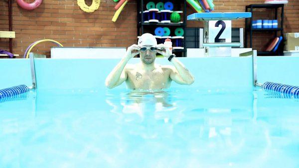 Fotografia di un nuotatore in acqua mentre si sistema gli occhialini a bordo piscina poco prima di iniziare l'allenamento
