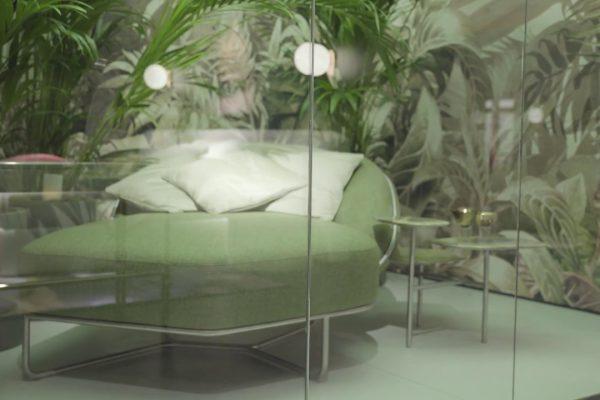 Immagine di una vetrina dello showroom di Clan Milano, con divano verde,cuscini e wall paper con piante tropicali