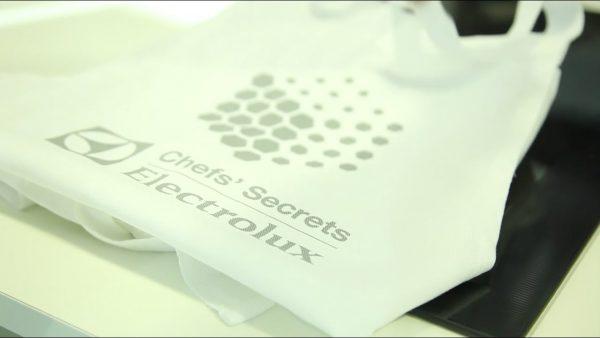 Fotografia di un grembiule da cucina poggiato su u fornello elettrico con logo Electrolux appoggiato a