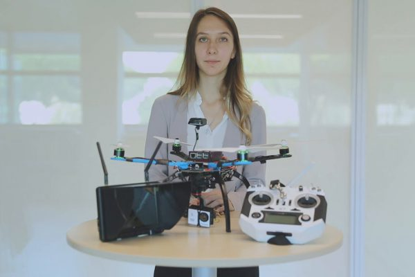 Fotografia di una donna con capelli biondi lunghi con le mai su un tavolino in cui sono esposti un drone, un joystick e un antenna