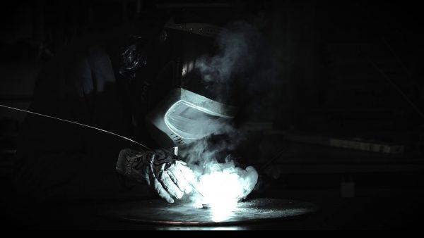 Immagine molto nuia di un artigiano con mascherina e guanti mentre utilizza un flessibile